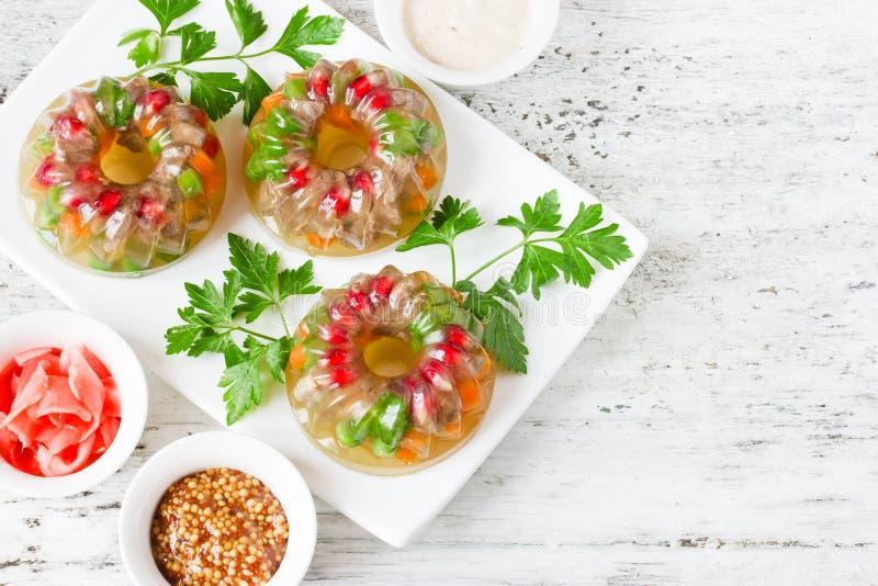 Fleisch Galantineaspik mit Karotte, Granatapfel, Erbsen, Petersilie an lizenzfreies stockfoto