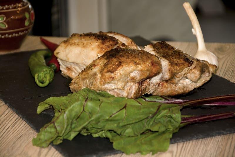 Fleisch gebacken im hölzernen Hintergrund des schwarzen Hintergrundes des Knoblauchs des roten Pfeffers des Ofens stockfotos