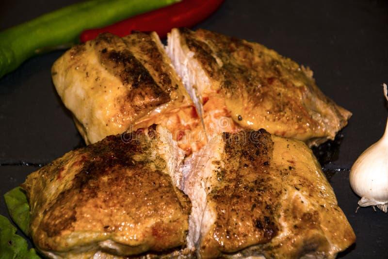 Fleisch gebacken im Hintergrundknoblauch des schwarzen Hintergrundes des grünen Paprikas des roten Pfeffers des Ofens hölzernen lizenzfreies stockbild