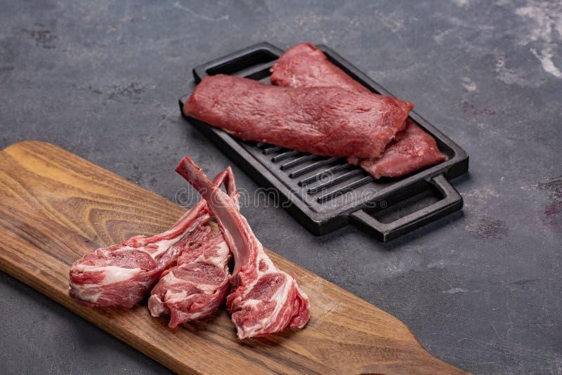 Fleisch-rohes frisches Hammelfleisch auf den Knochen Gewürzen Chesno und Rosemary auf einem schwarzen Hintergrund lizenzfreie stockfotografie