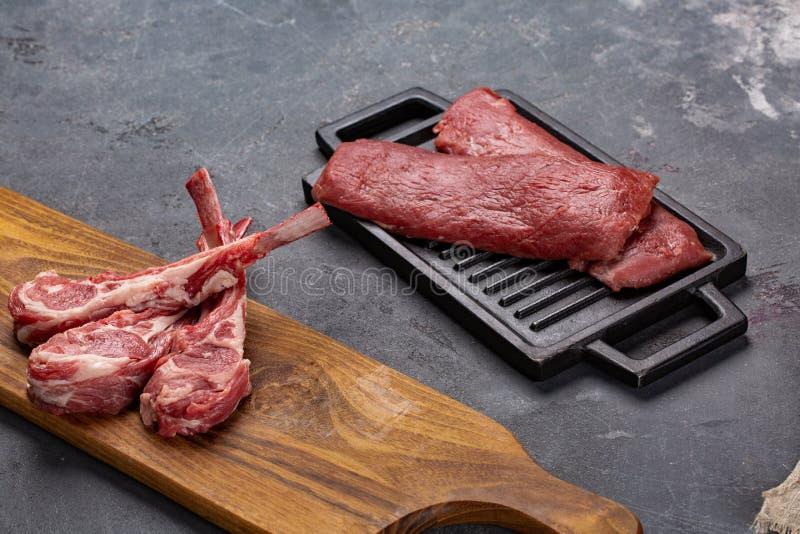 Fleisch-rohes frisches Hammelfleisch auf den Knochen Gewürzen Chesno und Rosemary auf einem schwarzen Hintergrund stockfoto