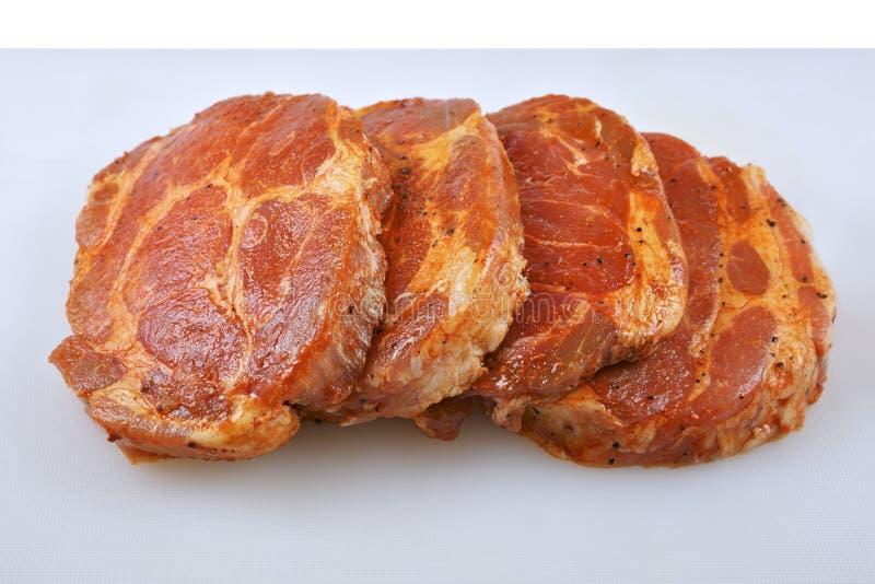 Fleisch, Schweinefleischhals in der Marinade und auf einem hackenden boardon, auf einem weißen Hintergrund stockbild
