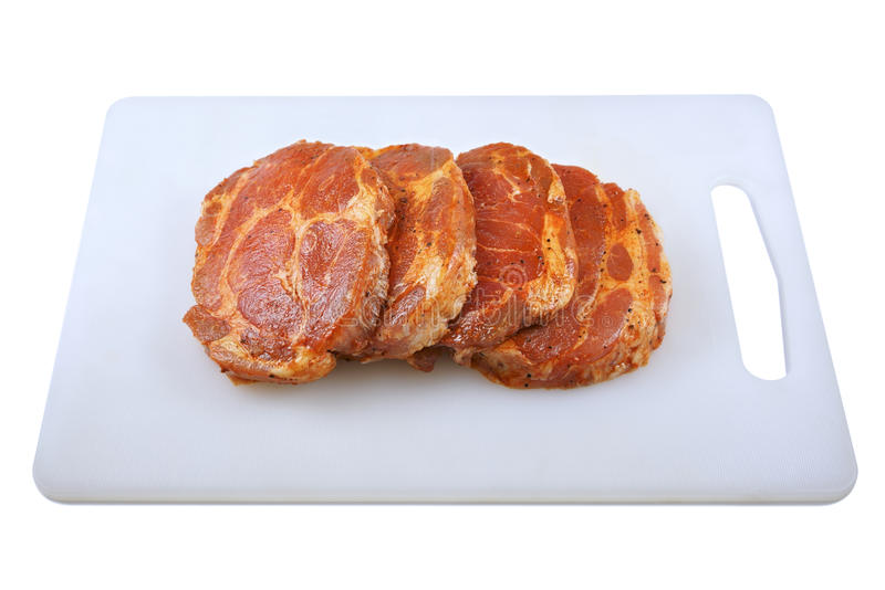 Fleisch, Schweinefleischhals in der Marinade und auf einem hackenden boardon, auf einem weißen Hintergrund stockfoto