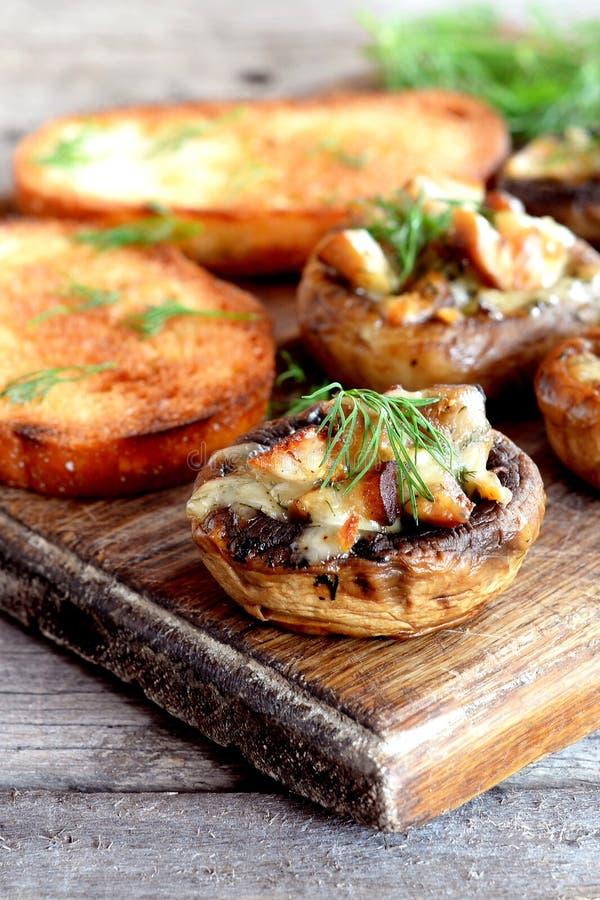Fleisch und Käse Julienne backte in den Pilzkappen, Toast auf einem hölzernen Brett nahaufnahme lizenzfreies stockbild