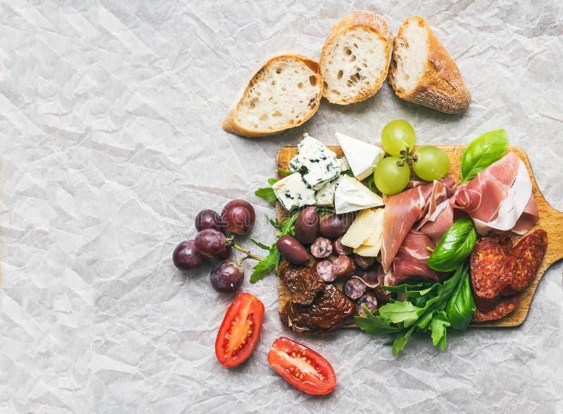 Fleisch- und Käseplatte auf rustikalem hölzernem Brett über einem Weißbuchba stockbild