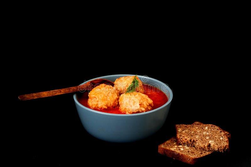 Fleischbälle in der Tomatensauce in der blauen Schüssel auf dunklem Hintergrund stockfotos