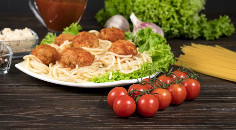 Fleischb?lle in Tomatensauce Bandnudeln und Basilikum auf einem h?lzernen Hintergrund stockbilder