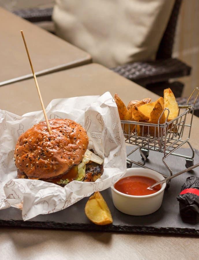 Fleischburger liegt beim Weißbuchverpacken Nahe bei gebratenen Kartoffeln und Soße stockfotos