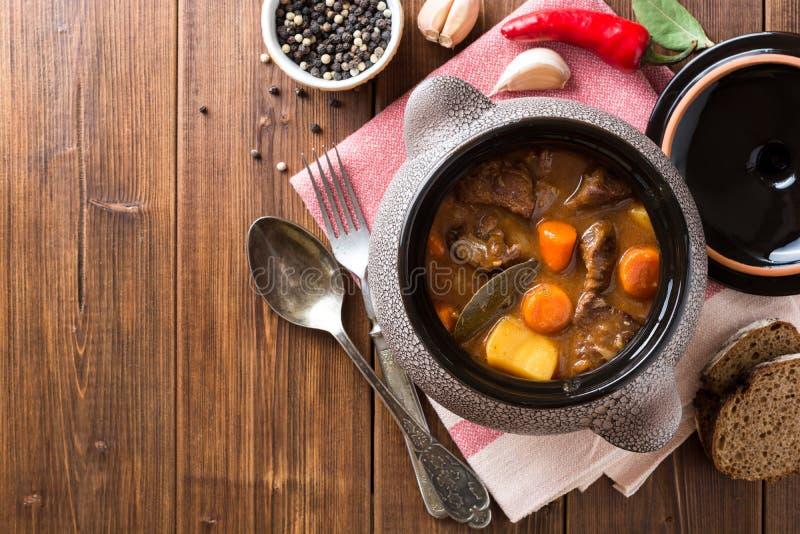 Fleischeintopfgericht mit Gemüse im keramischen Topf auf Holztisch lizenzfreies stockbild