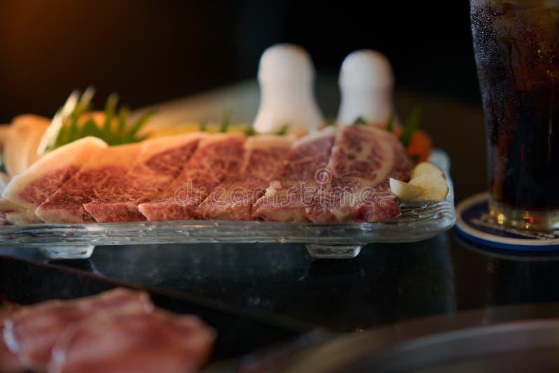 Fleischfleisch des Rindfleisches A5 in der Platte mit Grill und Unschärfepfeffer und -salz lizenzfreie stockfotografie