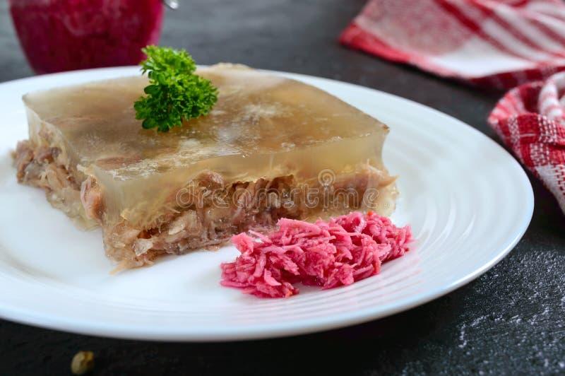 Fleischgelee mit würzigem Meerrettich auf einer weißen Platte auf einem schwarzen Hintergrund Slawischer traditioneller kalter Te lizenzfreie stockbilder