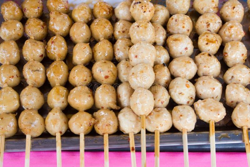 Fleischklöschen auf den Steuerknüppeln, eingetaucht in süße Paprikasoße stockfotografie