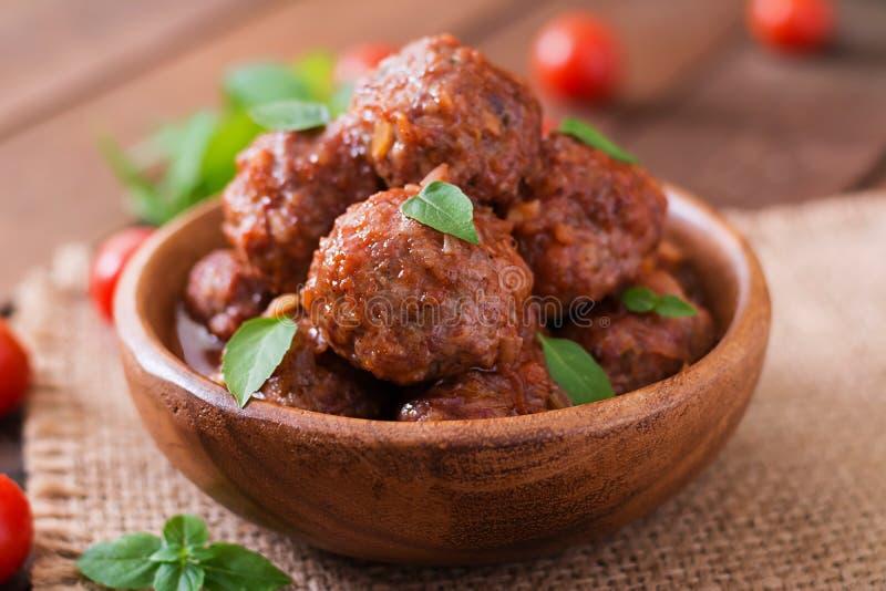 Fleischklöschen in der süßen und sauren Tomatensauce und dem Basilikum lizenzfreie stockbilder