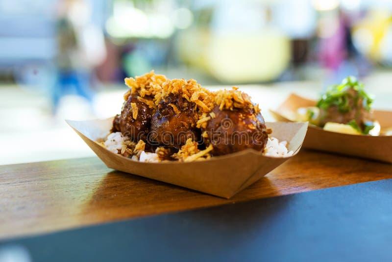 Fleischklöschen mit Reis und knusperiger Zwiebel in einem Lebensmittel-LKW lizenzfreie stockfotos