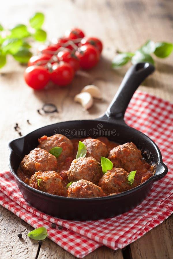 Fleischklöschen mit Tomatensauce in der schwarzen Wanne stockfoto
