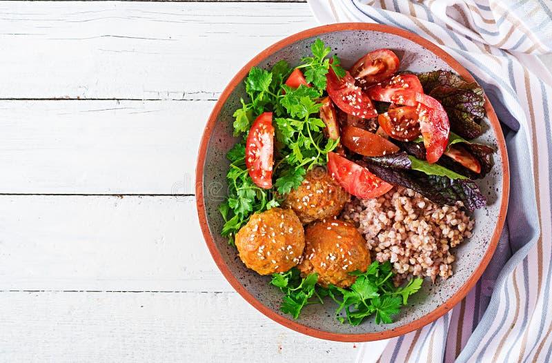 Fleischklöschen, Salat von Tomaten und Buchweizenbrei auf weißem Holztisch Gesunde Nahrung Weiße Platte mit Gewichtskala Buddha-S lizenzfreie stockfotos
