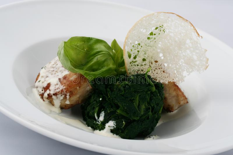 Fleischkoteletts mit gekochtem Spinat mit weißer Soße lizenzfreie stockbilder
