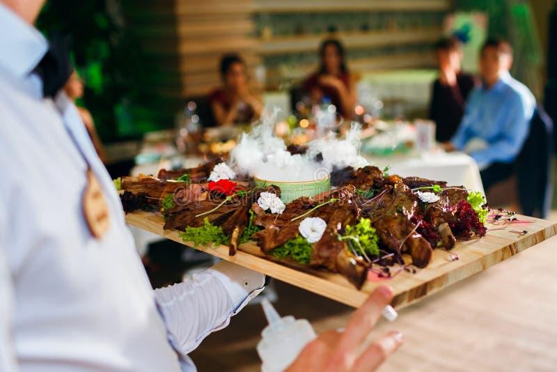Fleischrippen auf einem Behälter mit flüssigem Stickstoff, der Kellner liefert Nahrung im Hintergrund der Gäste, ein köstlicher T lizenzfreies stockbild