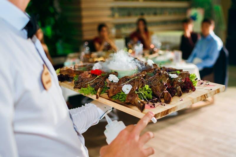 Fleischrippen auf einem Behälter mit flüssigem Stickstoff, der Kellner liefert Nahrung im Hintergrund der Gäste, ein köstlicher T stockfotografie