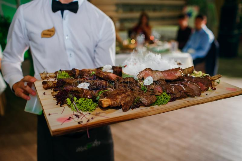 Fleischrippen auf einem Behälter mit flüssigem Stickstoff, der Kellner liefert Nahrung im Hintergrund der Gäste, ein köstlicher T stockbilder