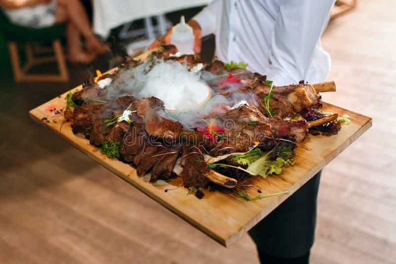 Fleischrippen auf einem Behälter mit flüssigem Stickstoff, der Kellner liefert Nahrung im Hintergrund der Gäste, ein köstlicher T stockfoto
