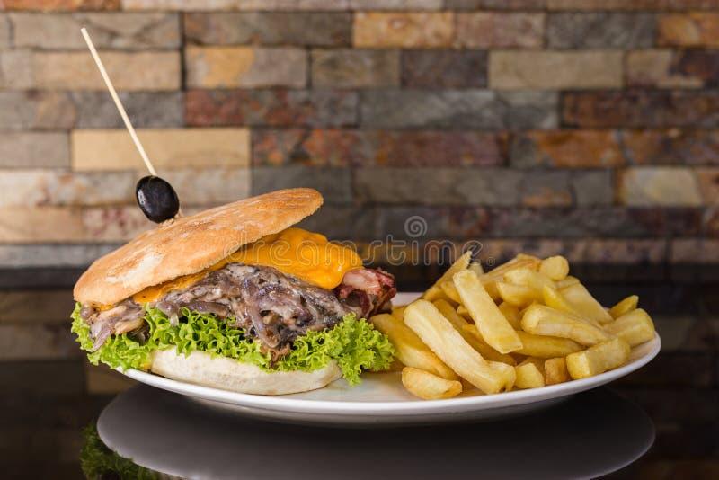 Fleischsandwich mit Cheddar-Käse, Pilzen, Zwiebel, Kopfsalat, Tomate, Speck und Pommes-Frites stockfotografie