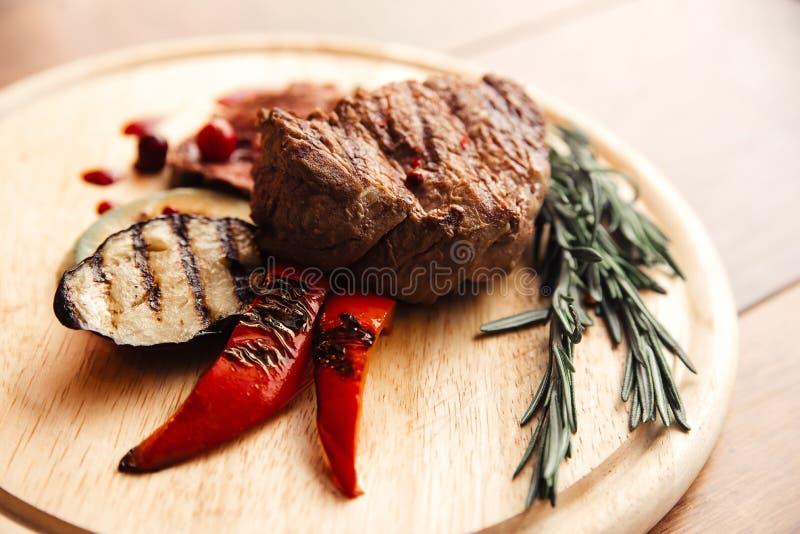 Fleischsteak auf einer h?lzernen Platte mit einer Beilage des gegrillten Gem?ses stockfoto