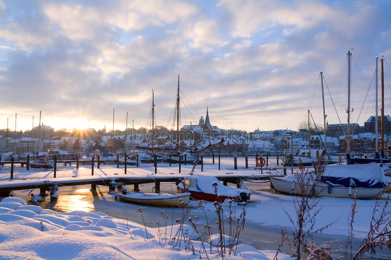 Flensburg at sunset. The city of Flensburg in northern Germany at sunset with sailboats in frozen water royalty free stock photos