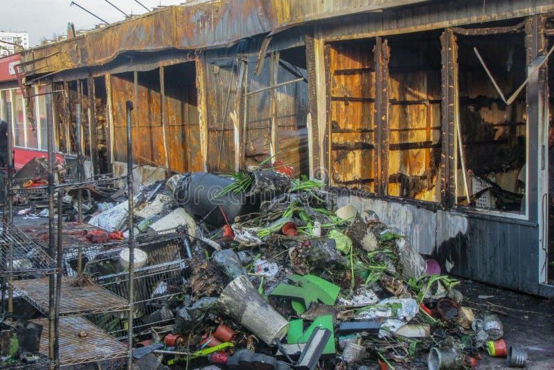 Flera bränt, förstört, litet shoppar av gatahandel efter branden Askaen och den bortskämda saker Fara till folk och royaltyfria bilder