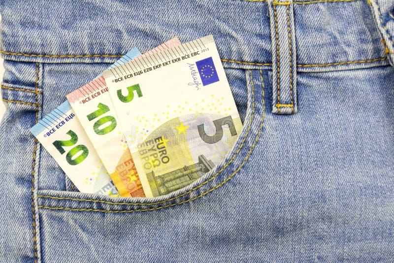 Flera euroräkningar sätts in in i jeansen stoppa i fickan arkivbild