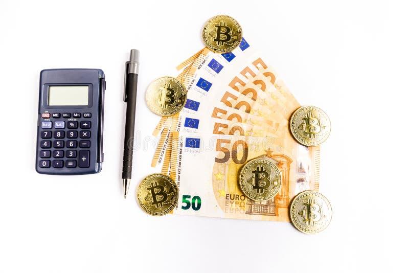 Flera guld- mynt för bitcoin bredvid några eurosedlar, en räknemaskin och en penna arkivbild