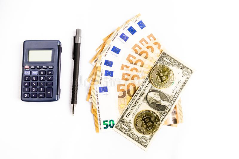 Flera guld- mynt för bitcoin bredvid några räkningar för euro och en dollar, en räknemaskin och en penna royaltyfri foto