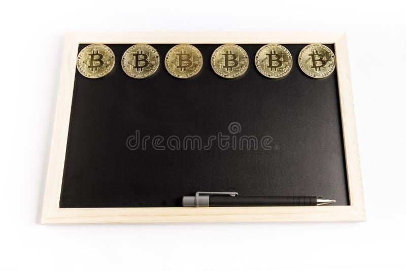 Flera guld- mynt f?r bitcoin bredvid en penna p? en svart svart tavla arkivfoto