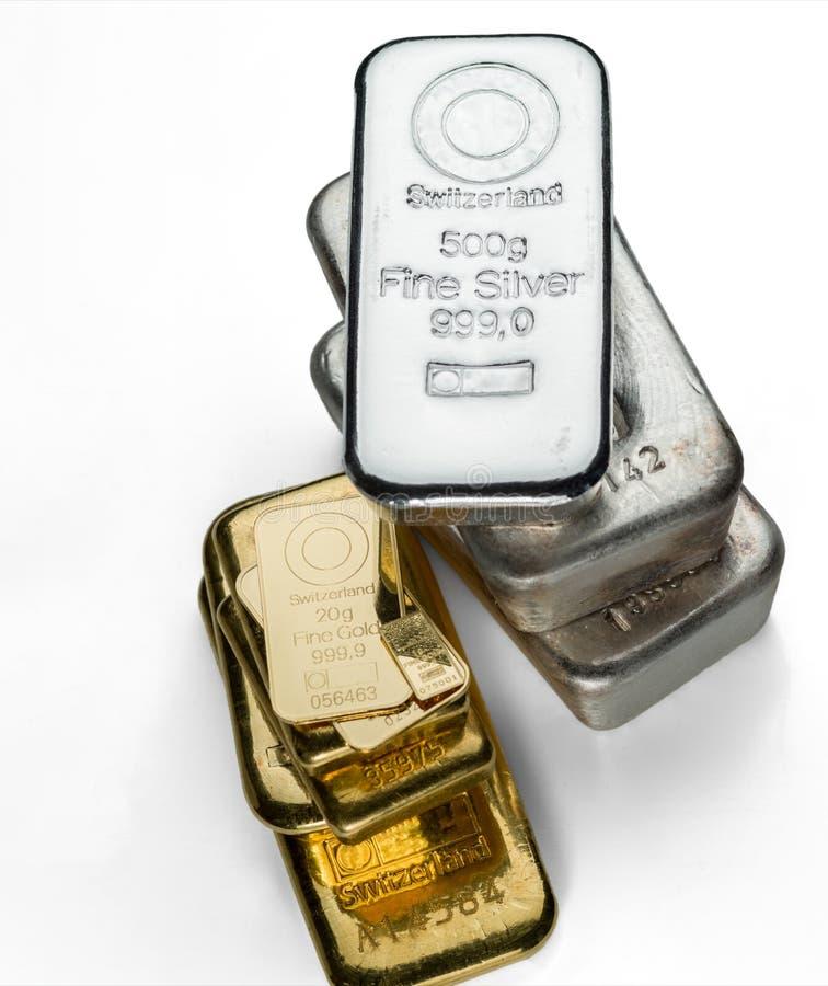 Flera guld- och silverstänger av olik vikt isoleras på en vit bakgrund royaltyfri bild