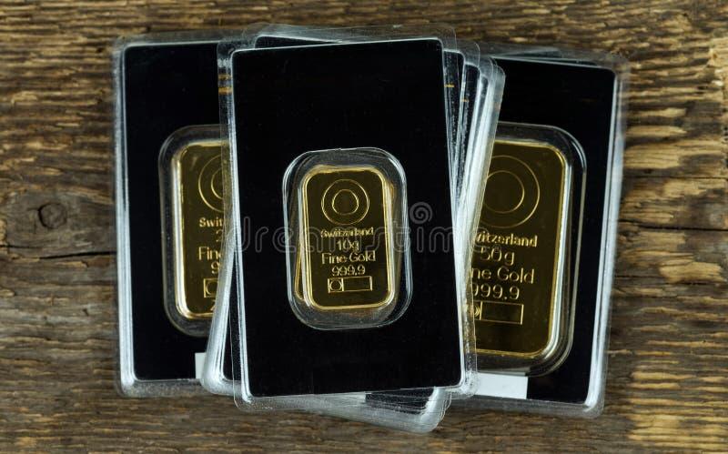 Flera guld- stänger av olik vikt i plast- förpacka på en träbakgrund royaltyfri foto