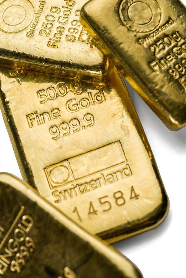 Flera guld- stänger för ensemble av olik vikt på en vit bakgrund arkivfoto
