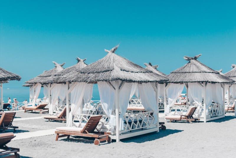 Flera härliga tält från solen på en sandig strand, mot bakgrunden av en härlig turkosblåtthimmel arkivbild