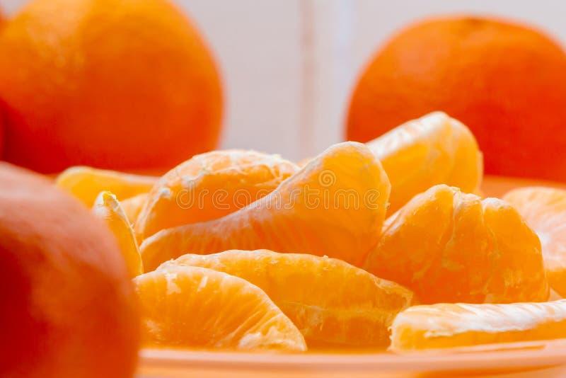 Flera hela och skalade mogna tangerin på en orange platta royaltyfri fotografi