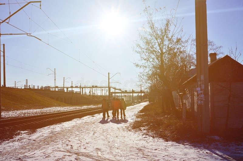 Flera järnväg arbetare i smutsiga orange likformig för signalerande är på vägen bredvid den järnväg linjen Drevbesättningen går a royaltyfria bilder