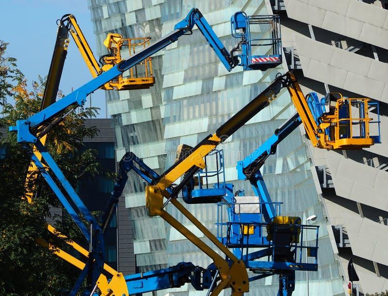Flera körsbärsröda plockare framme av en modern byggnad royaltyfri bild