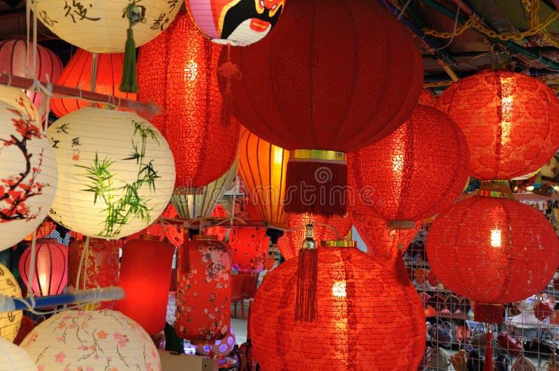 Flera kinesiska orientaliska asiatiska lyktor hängde upp till salu arkivfoton