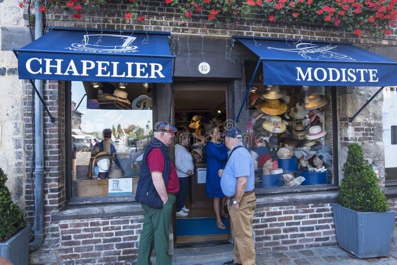 Flera män väntar på deras kvinnor nära hatten shoppar i Honfleur france normandy royaltyfria bilder
