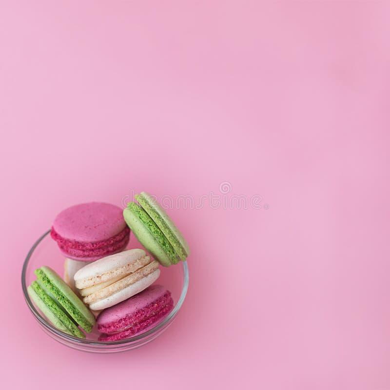 Flera mång--färgade macarons i en exponeringsglasplatta på en fyrkantig rosa bakgrund arkivfoton