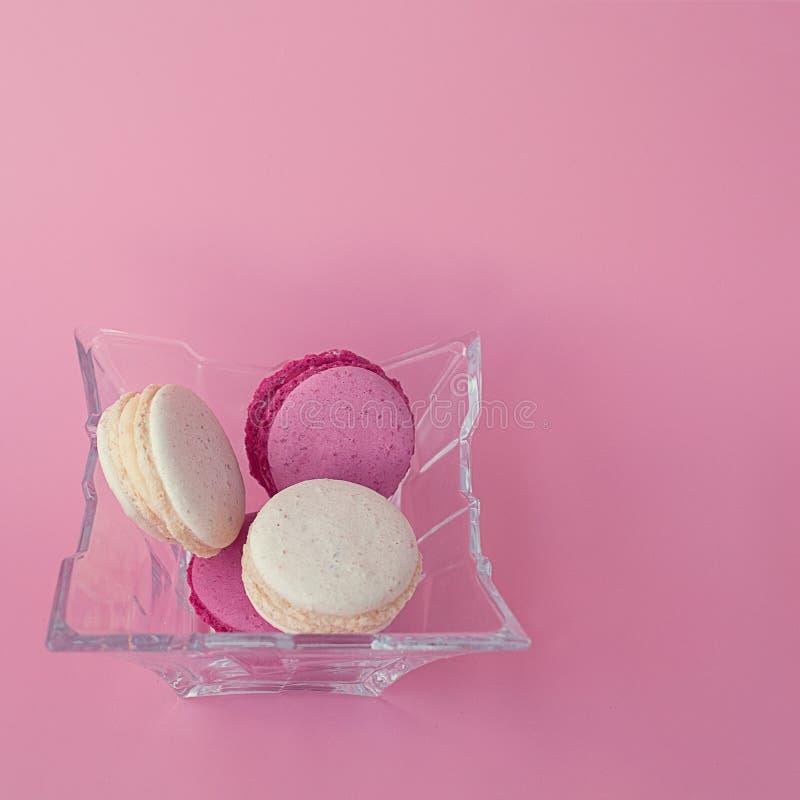 Flera mång--färgade macarons i en exponeringsglasplatta på en fyrkantig rosa bakgrund arkivbilder