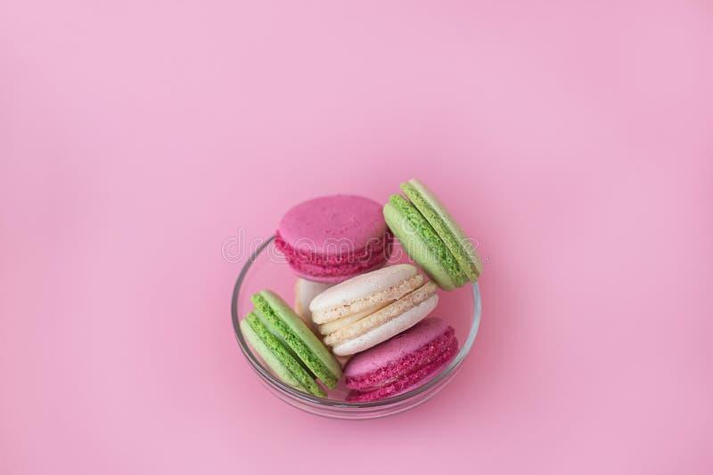 Flera mång--färgade macarons i en exponeringsglasplatta på en rosa bakgrund royaltyfri fotografi