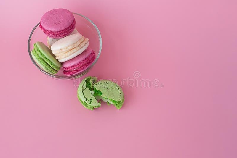 Flera mång--färgade macarons i en exponeringsglasplatta på en rosa bakgrund arkivfoto