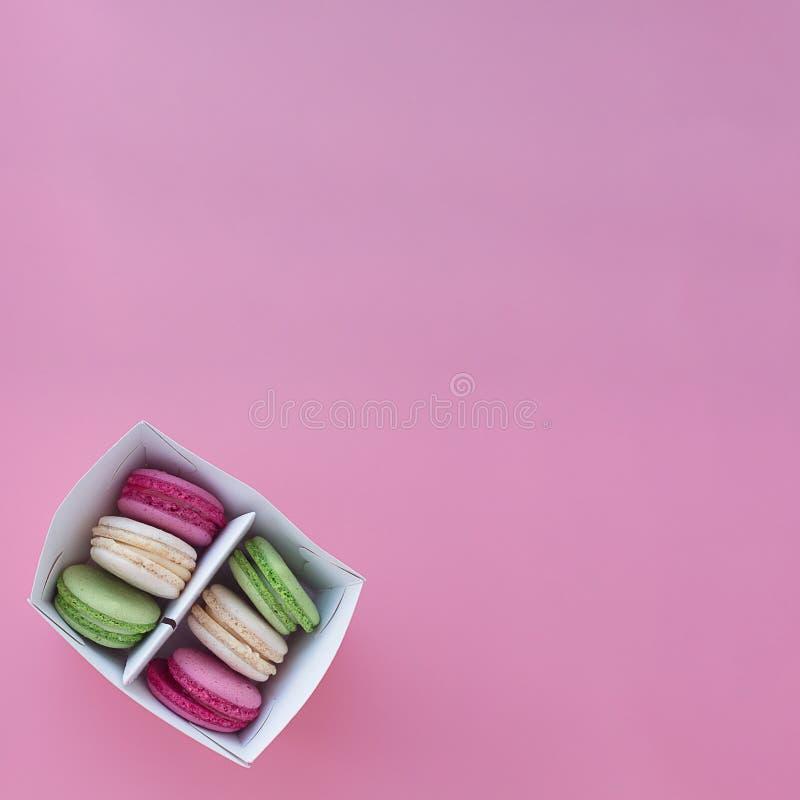 Flera mång--färgade macarons i en pappers- ask på en fyrkantig rosa bakgrund royaltyfri fotografi