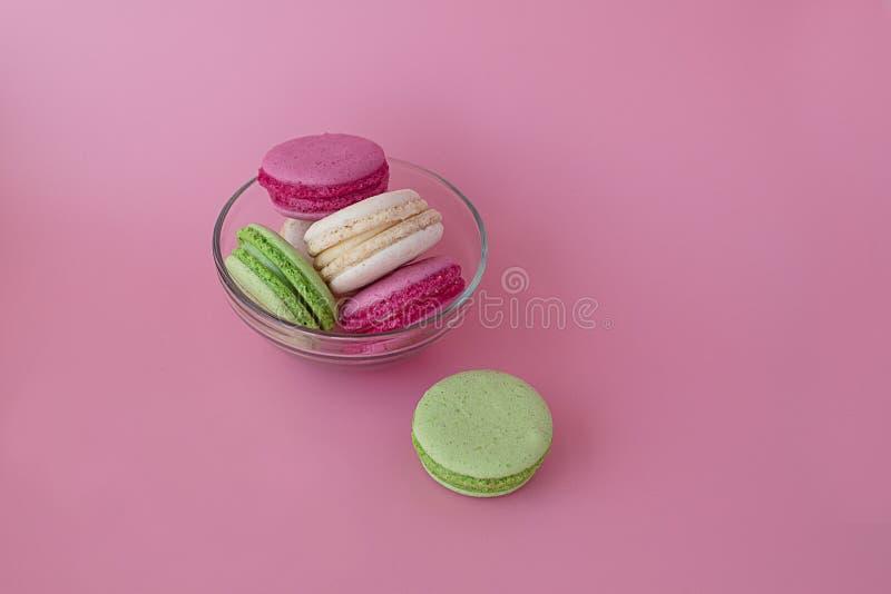 Flera mångfärgade macarons i en exponeringsglasplatta på en rosa bakgrund arkivbild