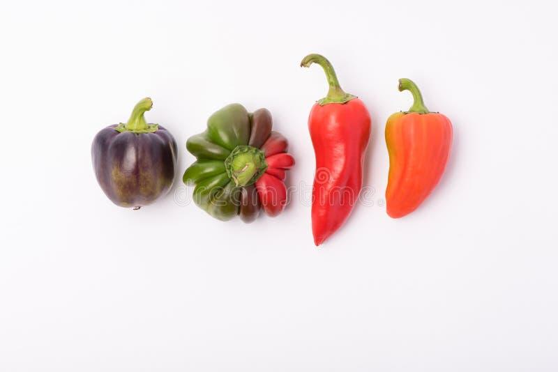 Flera mogen sötsak och varma peppar av rött och orange på en vit royaltyfri bild