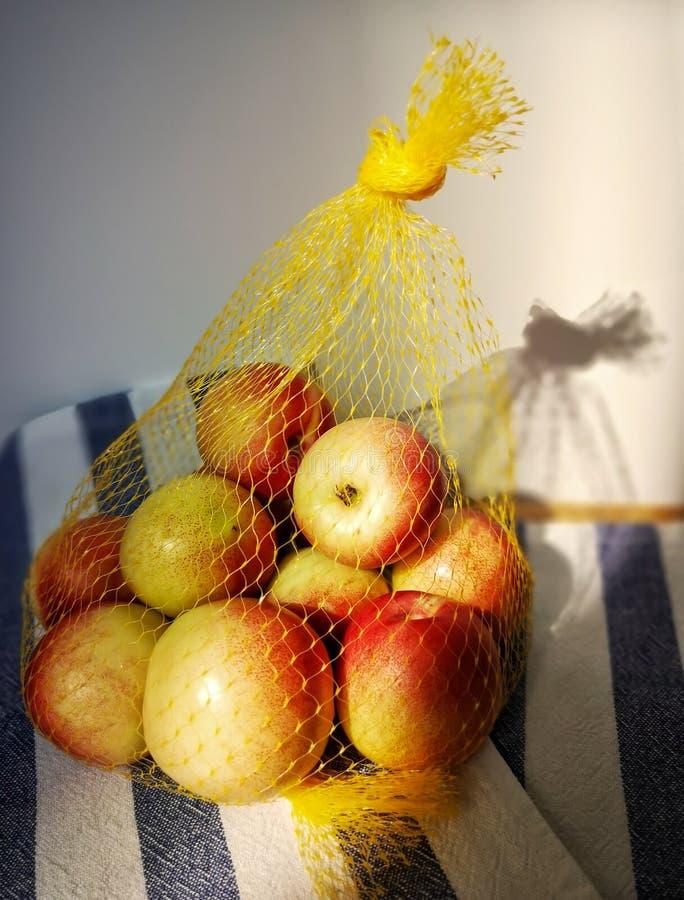 Flera nektariner, emballerade i ett återvinningsbart netto, ligger på en tabell på en linneservett Hårt ljus, skugga på väggen royaltyfria bilder